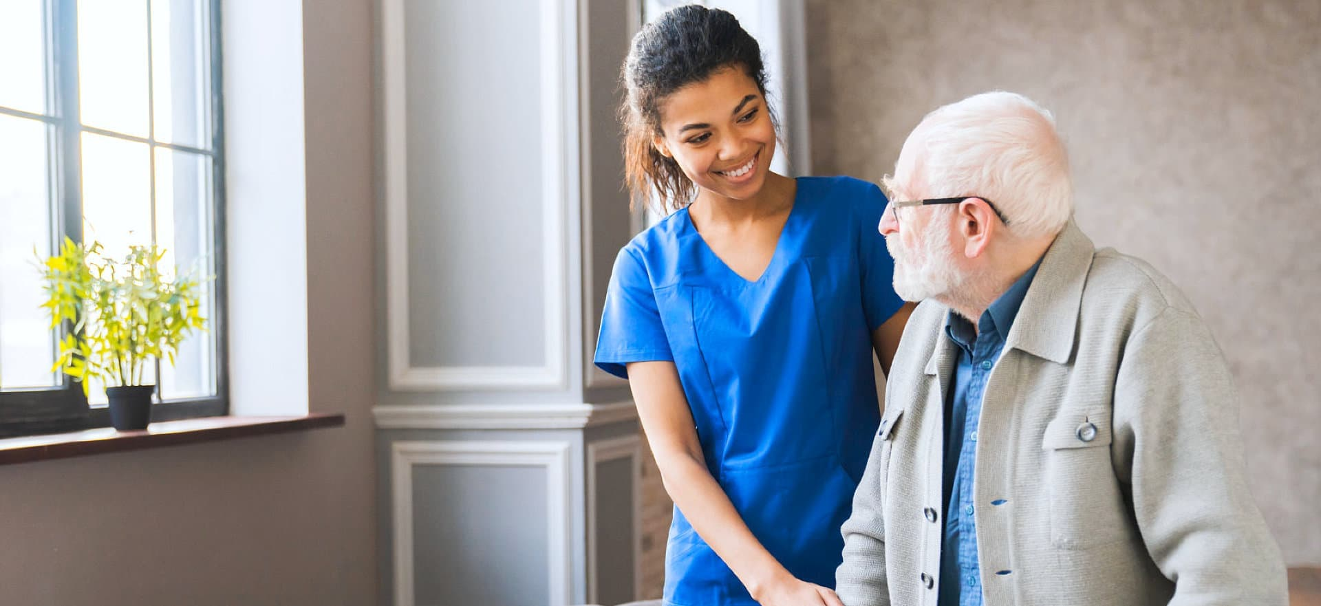 a nurse smiling at an elderly with glasses