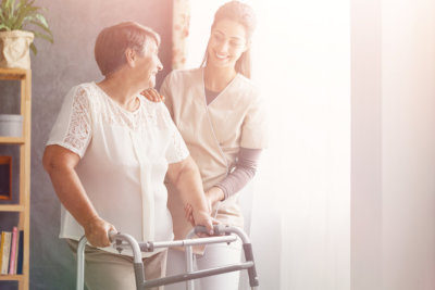 a nurse smiling at an elderly with crutches